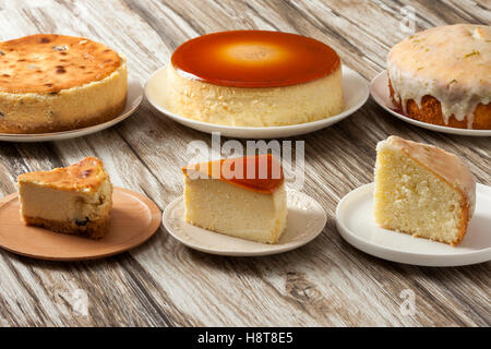 Three different kind of cheese cakes on wooden table - Stock Photo