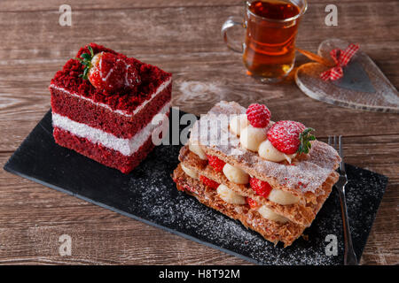 mille feuille dessert sweet slice red velvet cake with white frosting is garnished with strawberries - Stock Photo