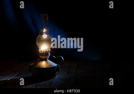 Old kerosene lamp on the rough wooden table. - Stock Photo