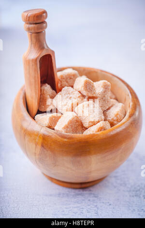 Brown cane sugar cubes in a wooden bowl. - Stock Photo