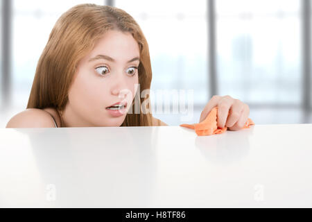 Woman in panic trying to clean germs from her desk - Stock Photo