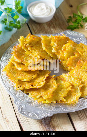 Homemade traditional potato pancakes, served with sour cream sauce. Hanukkah holiday meal on vintage wooden background. - Stock Photo