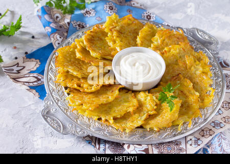 Homemade traditional potato pancakes, served with sour cream sauce, top view. Hanukkah holiday meal on vintage concrete - Stock Photo