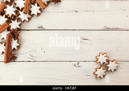 Christmas holidays background with cinnamon quills, star anise and star shaped cinnamon shortbread cookies on rustic - Stock Photo