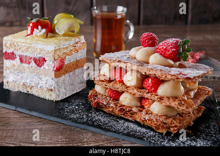 cream cake strawberry frosting mille feuille dessert sweet on black stone - Stock Photo