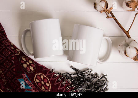 Two white mugs, pair of cups, Mockup. Cozy atmosphere, wooden background, cotton and wool decorations for winter - Stock Photo