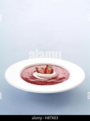 Delicious compot with red fruits and whipped cream in a plate - Stock Photo