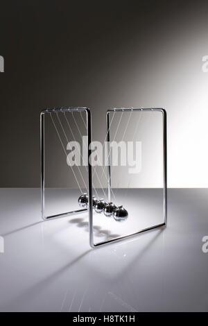 Chrome balancing spheres know as Newton's Cradle (pendulum) - Stock Photo
