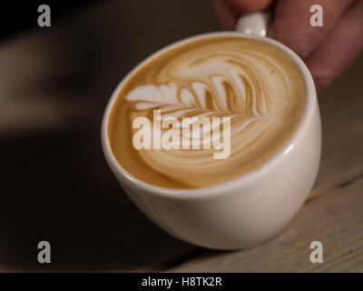 Making latte Art on a Cappucinno on a dark wooden background - Stock Photo