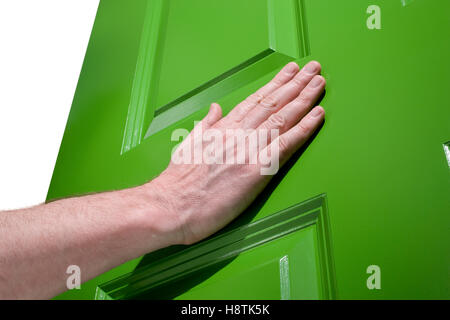 Man pushes a green door open with her hand - Stock Photo