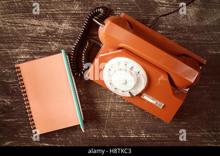 Old rotary telephone and spiral notebook on wooden table. - Stock Photo