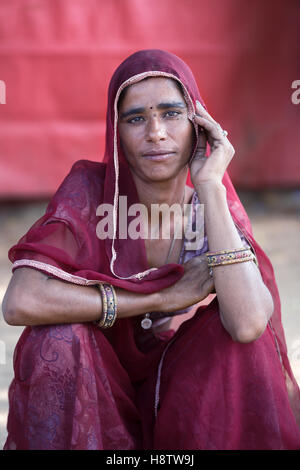 indian woman dressed in traditional scarf and sari, sits in front of the red tent and looks at the camera - Stock Photo
