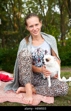 One white woman with brown hair resting in a park  his dog sitting on the rug barefoot - Stock Photo