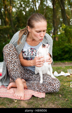 One white woman with brown hair resting in a park  his dog sitting on  rug  her bare feet trying to kiss him - Stock Photo