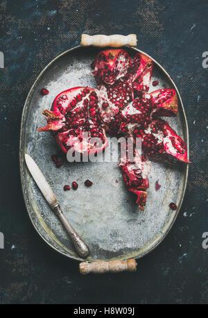 Fresh ripe pomegranate broken in pieces in metal tray - Stock Photo