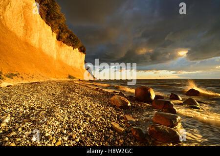 Chalk cliffs in early morning light, dark clouds, boulders, Jasmund National Park, Rügen, Mecklenburg-Western Pomerania - Stock Photo