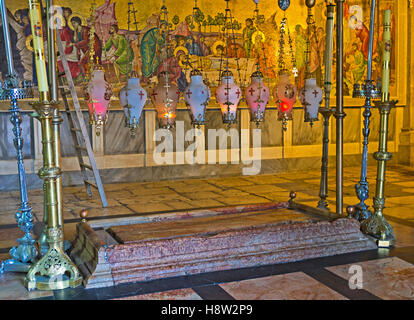 The Stone of Anointing in the Church of the Holy Sepulchre with the mosaic icon on the background - Stock Photo