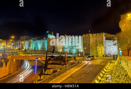 The evening city with the bright illuminated walls of the Jerusalem fortress, Israel. - Stock Photo