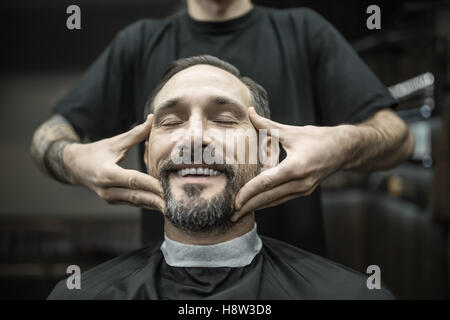 Face massage in barbershop - Stock Photo
