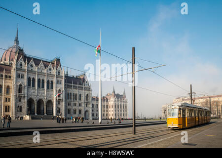 Building of the Budapest parliament. Yellow tram in front. - Stock Photo