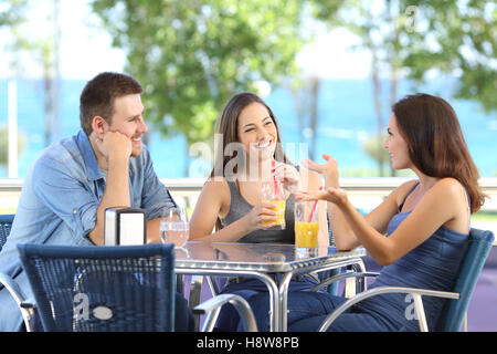 Group of three happy friends talking and refreshing with cold drinks in a bar terrace near of the beach - Stock Photo