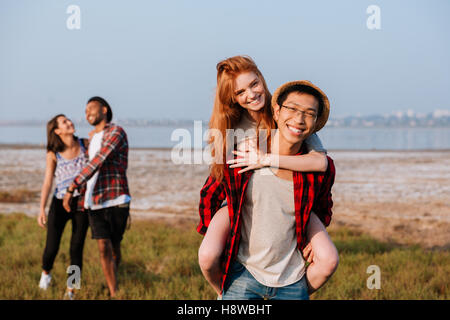 Two happy multiethnic young couples having fun outdoors - Stock Photo