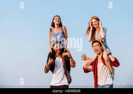 Two cheerful young women sitting on shoulders of their boyfriends outdoors - Stock Photo