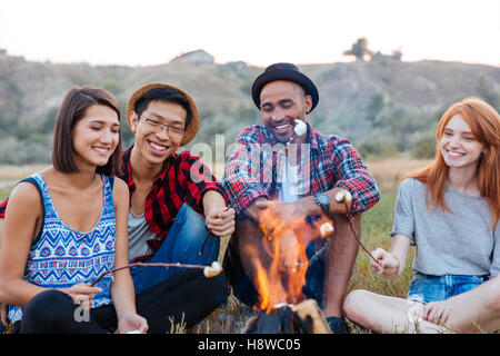 Group of happy young people sitting and roasting marshmallows on campfire outdoors - Stock Photo