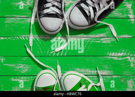 Two pairs of sneakers youth with untied laces on the green wooden surface, top view - Stock Photo