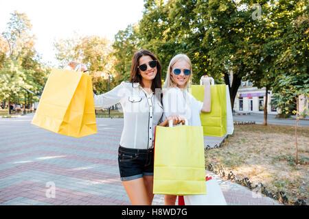 Two beautiful young women with shopping bags walking in the ctiy - Stock Photo