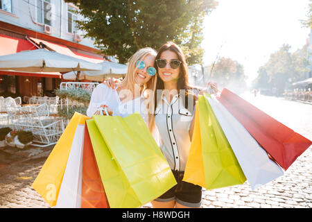 Two young women with shopping bags walking on the street together - Stock Photo