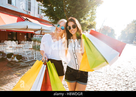 Two young fashion women with shopping bags walking along the street - Stock Photo