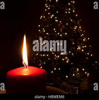 Glowing red candle in front of a Christmas tree - Stock Photo