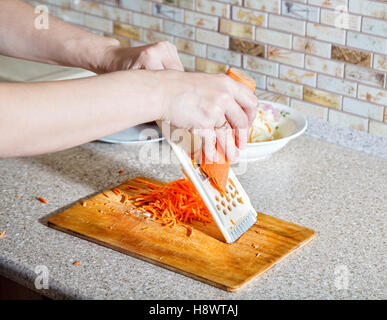 woman cooks the carrot on a grater hands closeup - Stock Photo