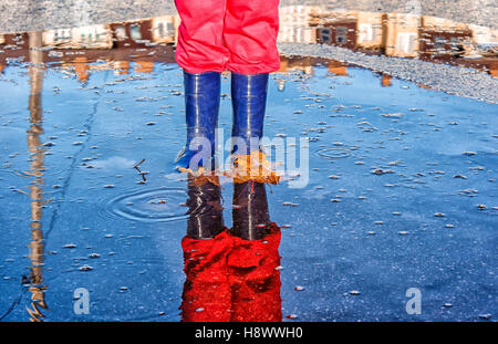legs of little girl in blue boots and red pants standing in a pool with fallen yellow leaves on autumn day closeup - Stock Photo