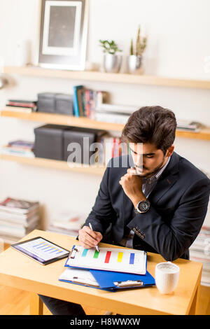 Young freelancer analyzes statistical report at the desk - Stock Photo