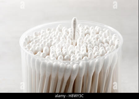 Cotton buds in a plastic container with a single bud raised above the others over a gray background in a close up - Stock Photo