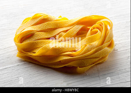 Roll of raw Italian tagliatelle pasta or ribbon noodles for traditional mediterranean cuisine in a close up view - Stock Photo