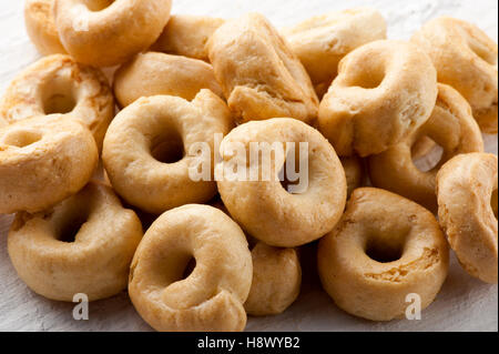 Pile of crunchy Italian taralli crackers for a tasty finger snack in a close up view on a white board - Stock Photo