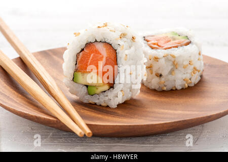 Two fresh salmon and avocado sushi uramaki served on a wooden plate with one standing upright to show the ingredients - Stock Photo