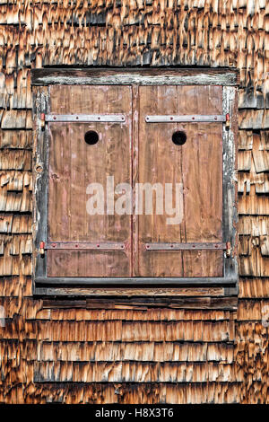 Closed wooden window shutters on typical swiss farmhouse - Stock Photo