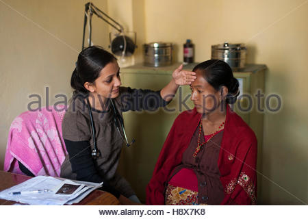 A General Practitioner consults a patient and checks her temperature at hospital in Nepal. - Stock Photo