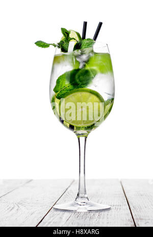 Cocktail in wine glass made with champagne, soda, lime, mint on white background. - Stock Photo