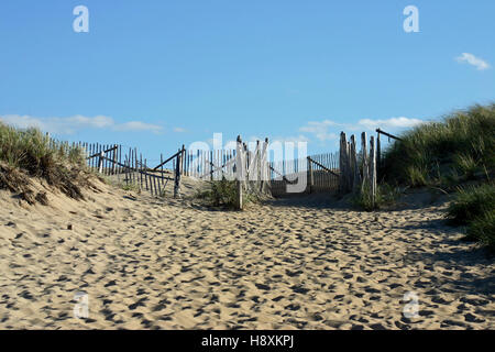 Rickety wooden fence, amid sand dunes, marking the entry way to Race Point Beach, Cape Cod, Massachusetts - Stock Photo