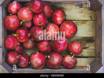 Turkish ripe pomegranates in rustic wooden box, copy space - Stock Photo