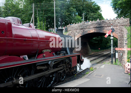 A steam locomotive waits at the lower quadrant semaphore starting signal at  on the West somerset Railway, UK - Stock Photo