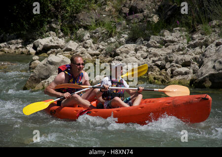 Tourism, water-sports. A father and his young son canoeing down the turbulent fast flowing waters of the Drôme River. - Stock Photo