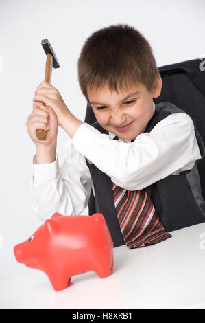 Boy, 8 years, robbing the piggy bank - Stock Photo