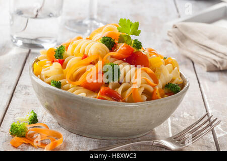 Fusilli pasta with colorful tomatoes, carrots and broccoli on a white wooden table Italian cuisine. - Stock Photo