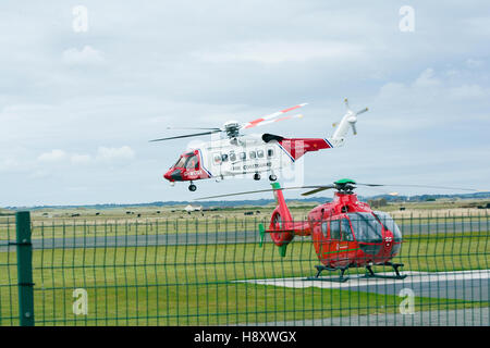 HM Coastguard Sikorsky S92 search and rescue helicopter and the Wales Air Ambulance at Caernarfon Airport. - Stock Photo